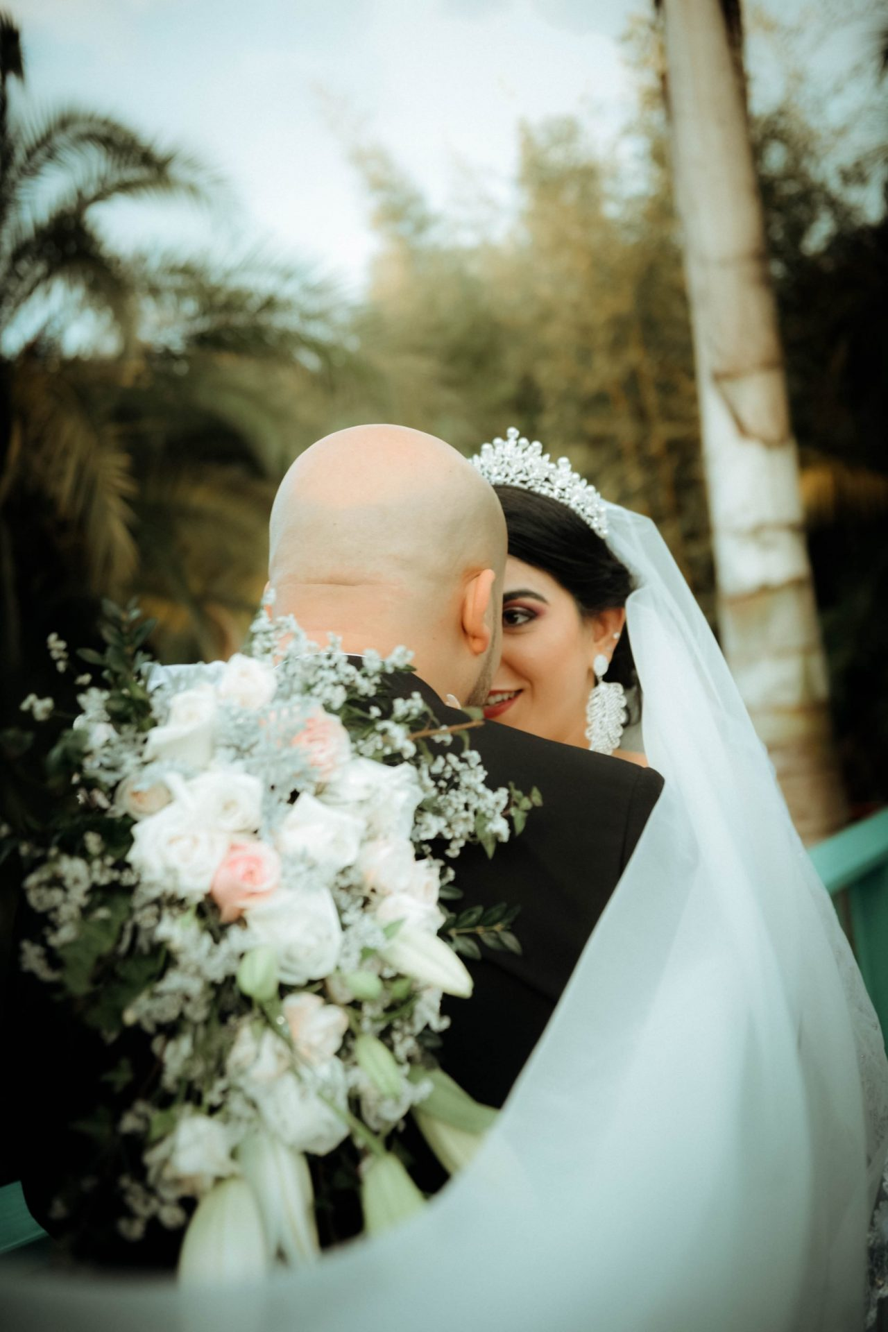 couple is standing and behind groom's back there are flowers, Wedding Photography of Sarah and Taher
