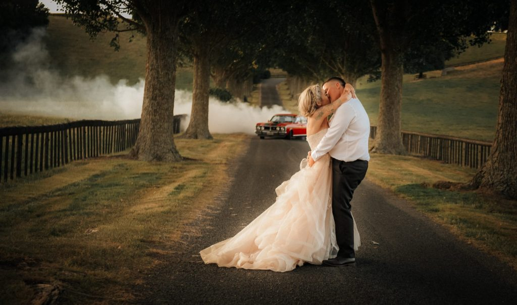 on the road, the couple are kissing each other, captured by Hamilton wedding photographer