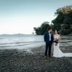 LaRosa Auckland Wedding Photography of couple is standing on a beach and is seeing each other during their Wedding Photography session