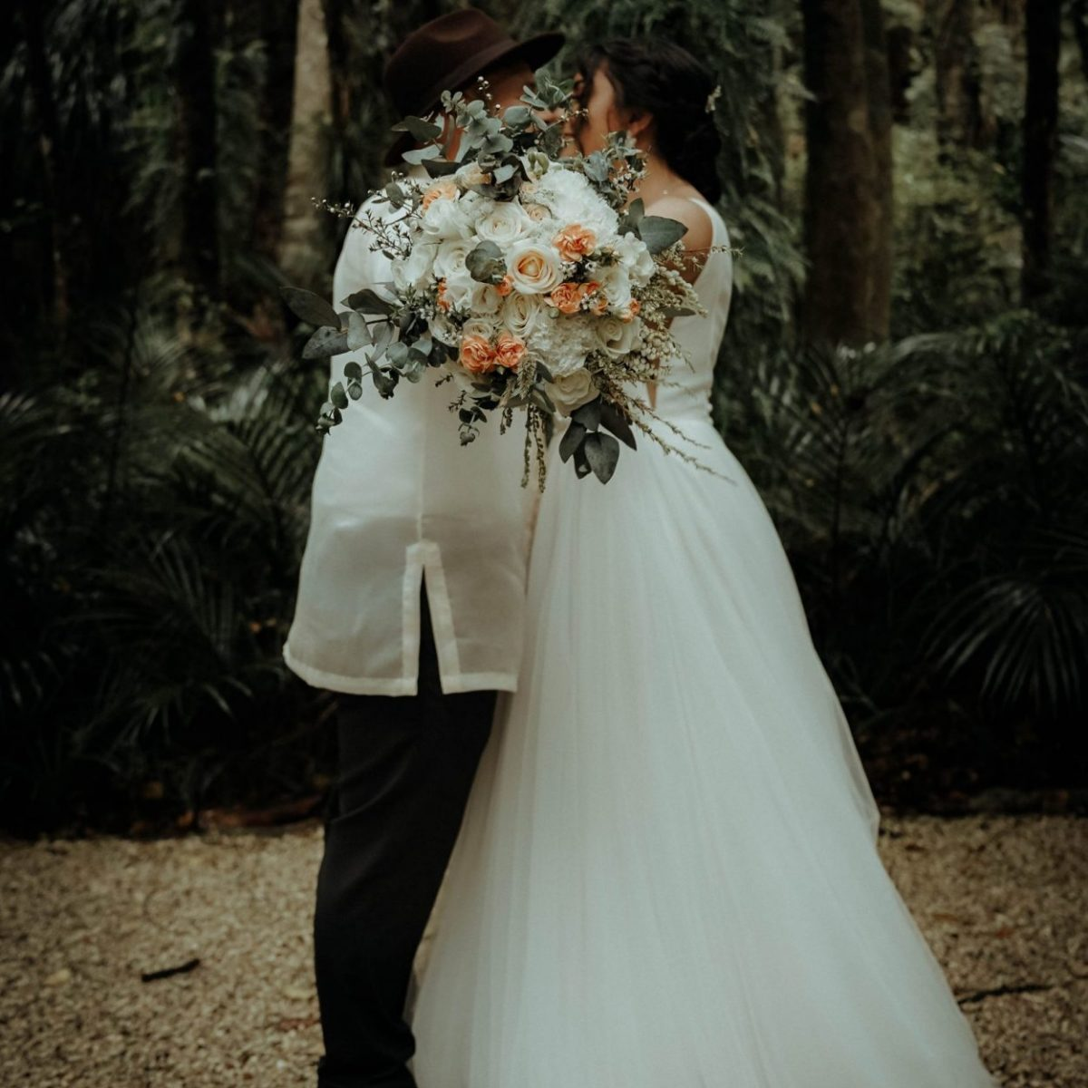 the couple is kissing each other and hiding it with flowers, Wedding Photography Auckland